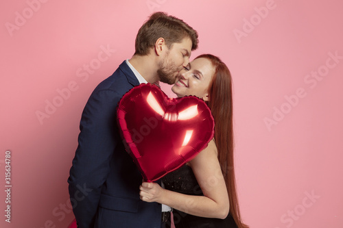 Happy holding balloons shaped hearts. Valentine's day celebration, happy caucasian couple on coral background. Concept of human emotions, facial expression, love, relations, romantic holidays. - 315634780