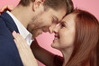 canvas print picture Valentine's day celebration, close up of caucasian couple's kissing and smiling on coral studio background. Concept of human emotions, facial expression, love, relations, romantic holidays.