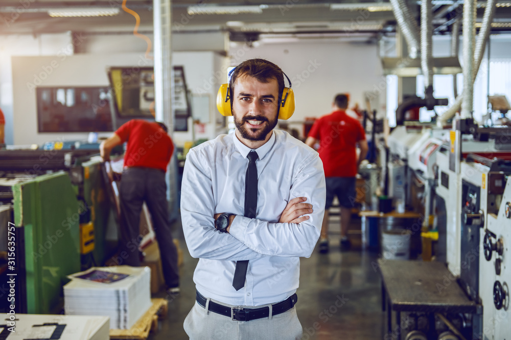 Fototapeta Attractive Caucasian bearded director in shirt and tie and with antiphons on ears standing with arms crossed in printing shop.