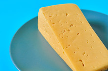 One Piece Of Cheese In Form Of Triangle On Gray Round Plate Lies On Blue Desk On Kitchen Or Market. Close-up