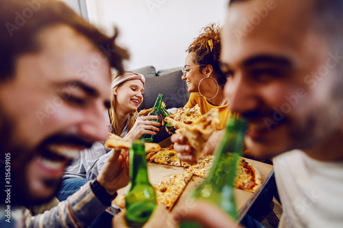Group of friends sitting on the floor in living room, drinking beer and eating pizza Canvas Print