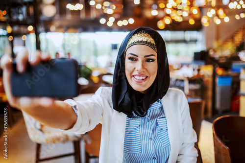 Cuadros en Lienzo  Charming modern smiling muslim woman with scarf on head sitting in cafe and taking selfie for social media
