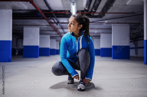 Young fit attractive caucasian sportswoman in tracksuit crouching and tying shoelace Tableau sur Toile