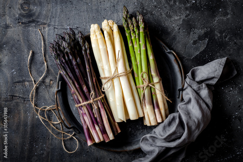 Fototapeta Bunches of fresh green, purple, white asparagus on vintage metal tray over dark grey rustic background. Top view, copy space obraz