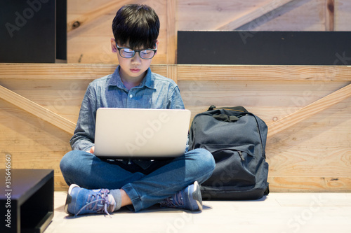 Photo Smart Asian preteen boy using computer laptop studying online lessons and coding with blue light blocking glasses