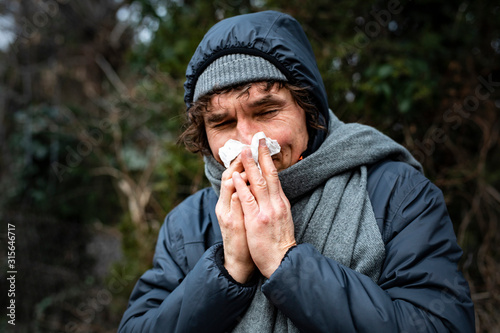 Obraz Man blowing his nose with a tissue when walking outdoor. Runny nose, infection, flu, viral diseases. - fototapety do salonu