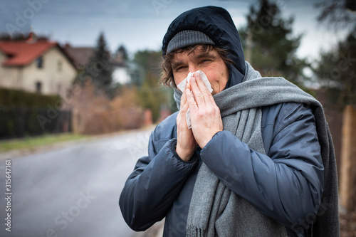 Fototapeta Sick man blowing his nose with a tissue. Infection, flu, viral diseases in autumn. obraz