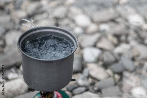 Boiling water in metal gray mug on river stones in campaign Wallpaper Mural