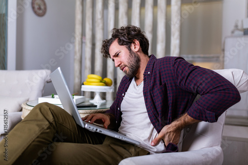 Fotomural Tired man freelance worker stretch in sofa suffer from sitting long in incorrect posture, male employee have back pain or spinal spasm working in uncomfortable position