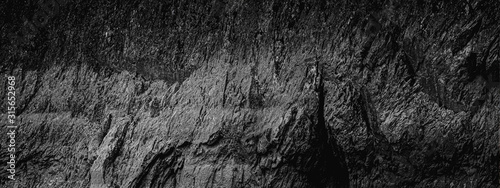 Dark Aged Shabby Cliff Face And Divided By Huge Cracks And Layers. Coarse, Rough Gray Stone Or Rock Texture Of Mountains, Wide And Panoramic Background For Text On Theme Geology And Mountaineering.