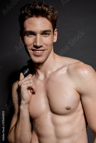 smiling sexy young man with muscular torso and biker jacket on black background Fototapeta