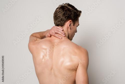 Obraz na plátně back view of man having neck pain isolated on grey
