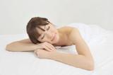 裸で寝転ぶ若い女性