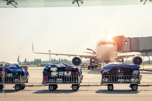 Luggage motion blurred trolley cart going fast delivering passenger baggage to modern plane on taxiway at airport on bright sunny day Canvas Print