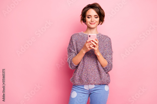 Fototapeta Portrait of her she nice attractive lovely pretty cute winsome focused confident cheerful brown-haired girl holding hands cell sending sms isolated over pink pastel color background obraz
