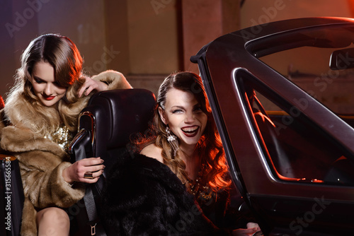 Famous retro beautiful young women in a black convertible car, ride to a party Canvas Print
