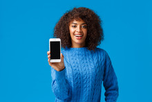 Look At My Score. Happy And Proud, Good-looking African-american Woman Browsing Dating App, Showing Smartphone Screen Camera, Take A Look, Standing Blue Background In Winter Sweater
