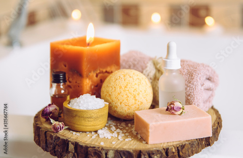 Obraz na plátně Home spa products on wooden disc tray: bar of soap, bath bomb, aroma bath salt, essential and massage oils, candle burning, rolled towel inside bathroom by tub, water running