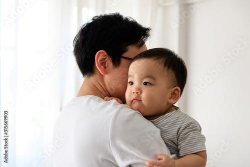 Fotografia  Portrait of Father Holding Baby Son In home. White tone