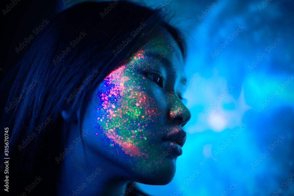 Fototapeta Beautiful young woman dancing and making party with fluorescent painting on her face. Neon facial portraits