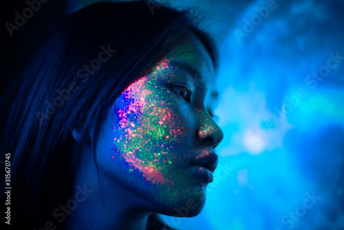 Beautiful young woman dancing and making party with fluorescent painting on her face. Neon facial portraits - 315670745