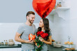 Attractive young couple dressed in casual outfit celebrating St. Valentine's day together at home sharing presents in cozy kitchen
