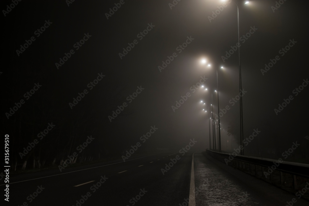 Fototapeta Empty road fog at night. Along the road lights are on.