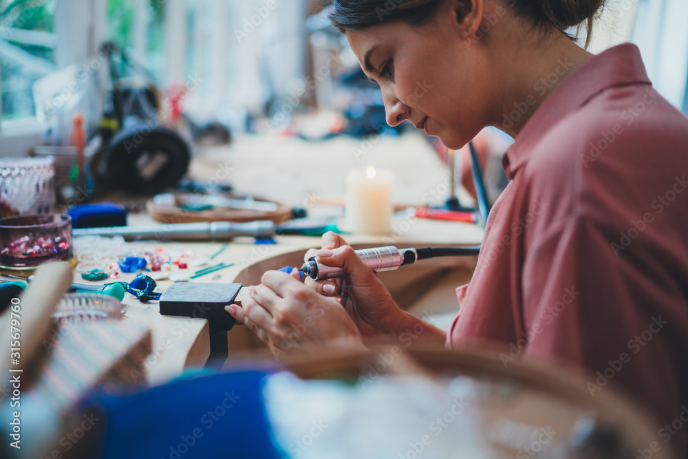 Fototapeta Side View Shoot of Young Professional Jewelry Maker Working in Own Workshop, Creative People Handcraft Handmade Process