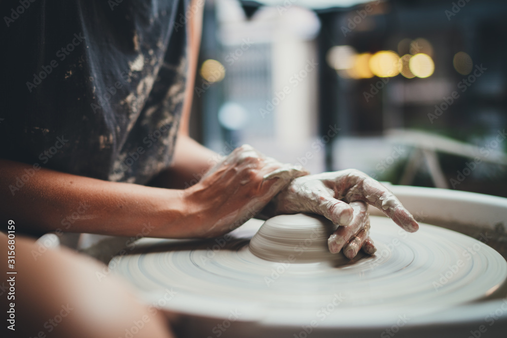 Fototapeta Side View of Young Creative Girl Student Makes her First Vase in a Pottery Class Sitting at a Pottery Wheel in a Cozy Workshop, Handcrafted Product Hobby Art