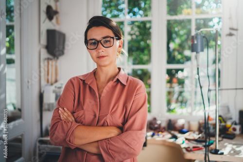 Portrait of young female entrepreneur working in her studio, young professional manager wearing casual clothes working in