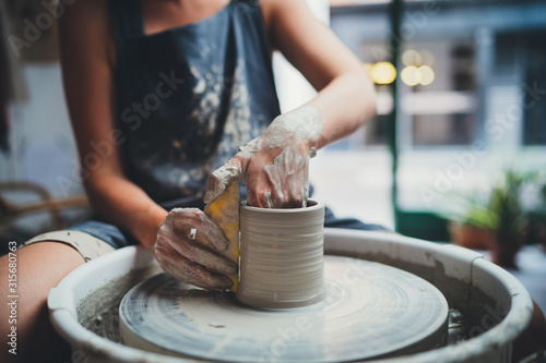 Fototapeta Cropped Image of Unrecognizable Female Ceramics Maker working with Pottery Wheel in Cozy Workshop Makes a Future Vase or Mug, Creative People Handcraft Pottery Class  obraz