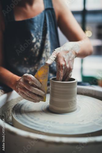 Fototapeta Vertical Image of Professional Female Maker Ceramics Working with Pottery Wheel