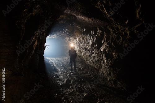 Underground gold mine shaft tunnel drift with miner and light