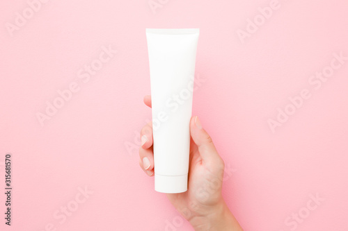 Foto Young woman hand holding and showing white tube on pastel pink table