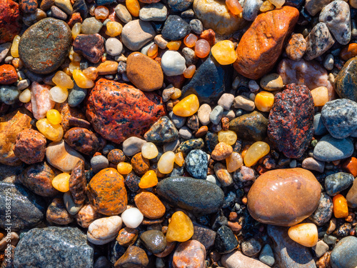 Photo Small amber stone and pebbles on the sandy beach