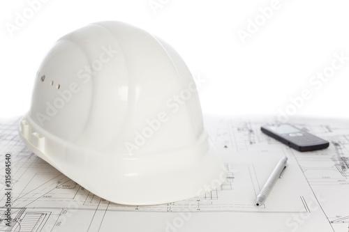 Photo Hard hat, cell phone and pen on construction plan