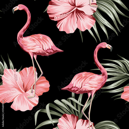 Tropical pink hibiscus and flamingo floral green palm leaves seamless pattern black background. Exotic jungle wallpaper.