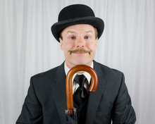 British Gentleman In Dark Suit And Bowler Hat Smiling Cutely Over Handle Of Umbrella. Laurel And Hardy Manner. Kind And Quirky Gentleman.