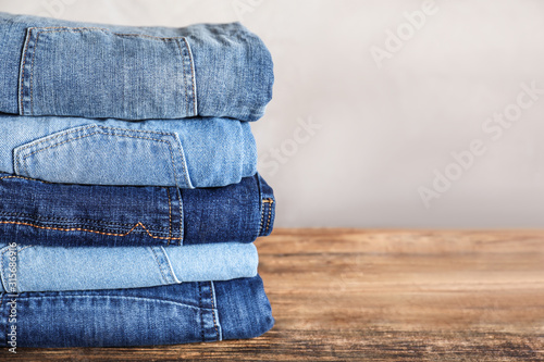 Fotografie, Obraz Stack of different jeans on wooden table. Space for text