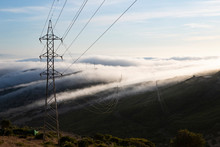 Spain, Electricity Pylon Against Hills Of Gibraltar Shrouded In Clouds