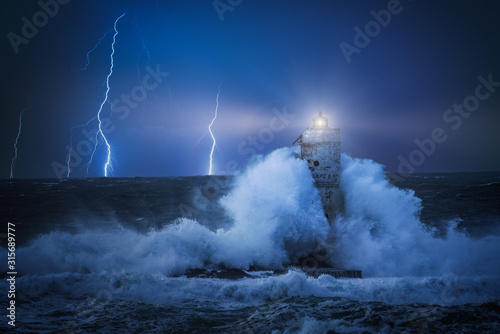 Lighthouse at night in the middle of a storm Fototapeta