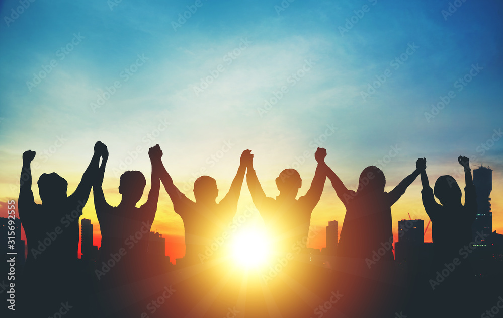 Fototapeta Silhouette of group business team making high hands over head in sunset sky in city for business success and teamwork