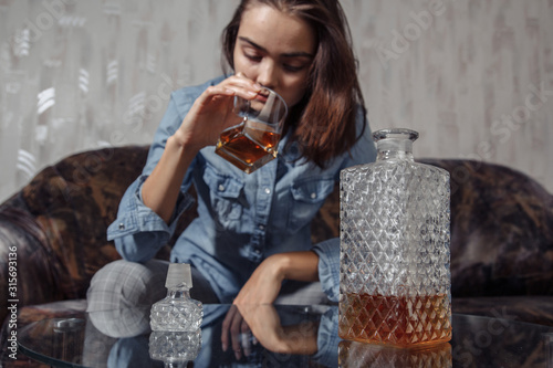 Cuadros en Lienzo Young female drinks alcoholic beverage in depression and stress
