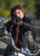 A Woman In A Black Leather Biker Jacket With A Carbine Rifle On A Chopper Motorcycle In Greece On A Road In The Forest In The Mountains