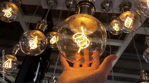 Obraz Round filament led bulbs, hand holding light bulb, background - fototapety do salonu