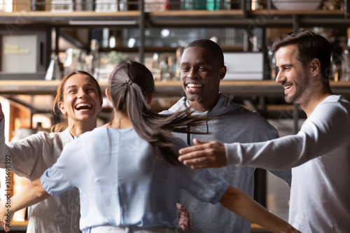 Happy diverse friends giving hug meeting girlfriend in cafe