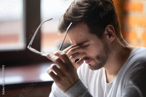 Photo Exhausted male massage eyes suffering from headache