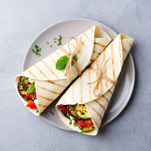 Wrap Sandwich With Grilled Vegetables And Feta Cheese On A Plate. Grey Background. Top View