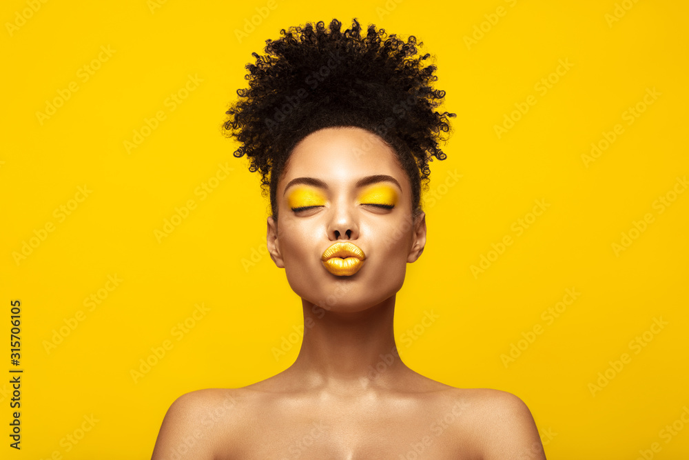 Fototapeta Enjoyed African American Fashion Model portrait . Satisfied Brunette young woman with afro hair style and closed eyes show kiss,creative yellow make up, lips and eyeshadows on colorful background.
