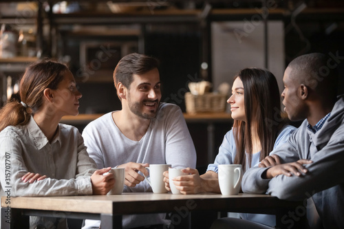 Tablou Canvas Diverse young people meeting in cafe drinking coffee